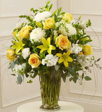 A vase filled with mums, roses, stock