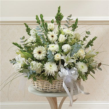 floral basket is bursting with all white flowers such as, gerbera daisies, white roses, white lilies, white carnations, a white bow and a variety of greens.