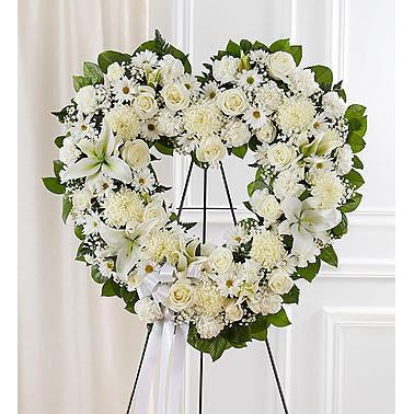 The heart comes with all white flowers such as: roses, lilies, mums, daisy poms