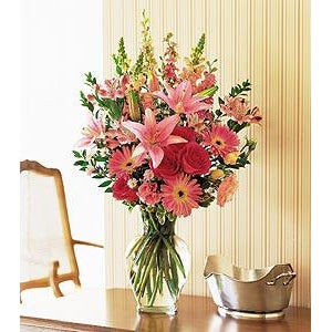 beautiful pink roses, gerbera daisies, alstroemeria  and a variety of fresh spring flowers in a designer glass vase.