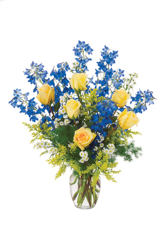 vase is filled with yellow roses, blue delphinium
