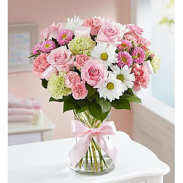 Celebrate the new arrival of a baby girl with this bright and cheery display of flowers. A unique bouquet of gorgeous pink roses. pink mini-carnations, white daisy poms decorated with a beautiful pink ribbon