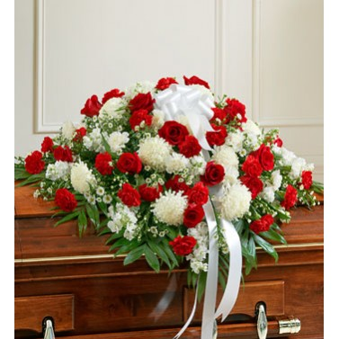 A half couch casket spray of roses, carnations, mums and more.