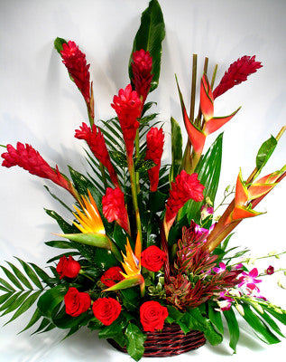 A basket filled with Birds of paradise, ginger, orchids, lush tropical greens, and more.
