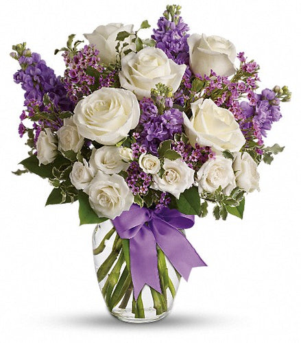 bouquet of pure white roses, purple stock, and purple filler.