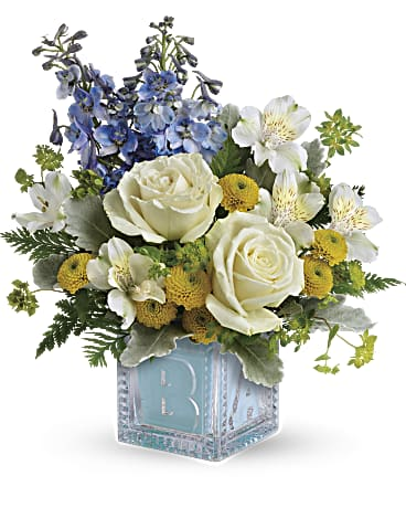 Celebrate a new life with this luxurious bouquet of roses, mums and blue delphinium, white alstroemeria, yellow button spray chrysanthemums, arranged with bupleurum, dusty miller, and leatherleaf fern in a darling glass baby block keepsake cube.