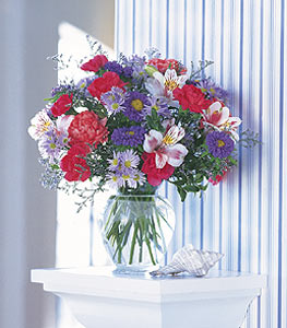 A vase filled with purple aster, white alstroemeria, pink carnations, and more.