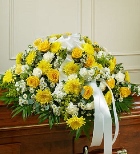 A beautiful bright array of mostly yellow and white soft-hued roses, carnations, mums and more accented with a beautiful white ribbon makes this spray an elegant remembrance of your loved one.