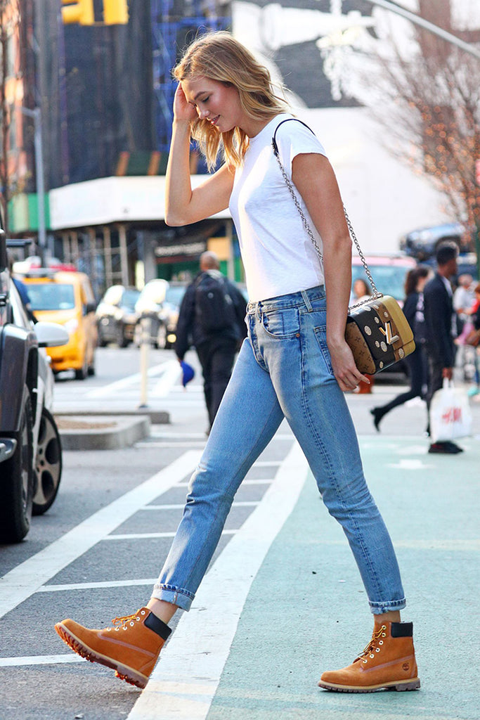 Street Style Photo of woman in white tee, blue jeans and hiking boots
