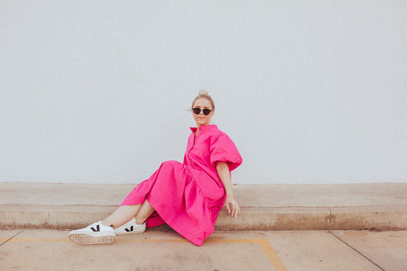 Abby seated wearing Fushcia Pink puff sleeve dress by Nice Martin