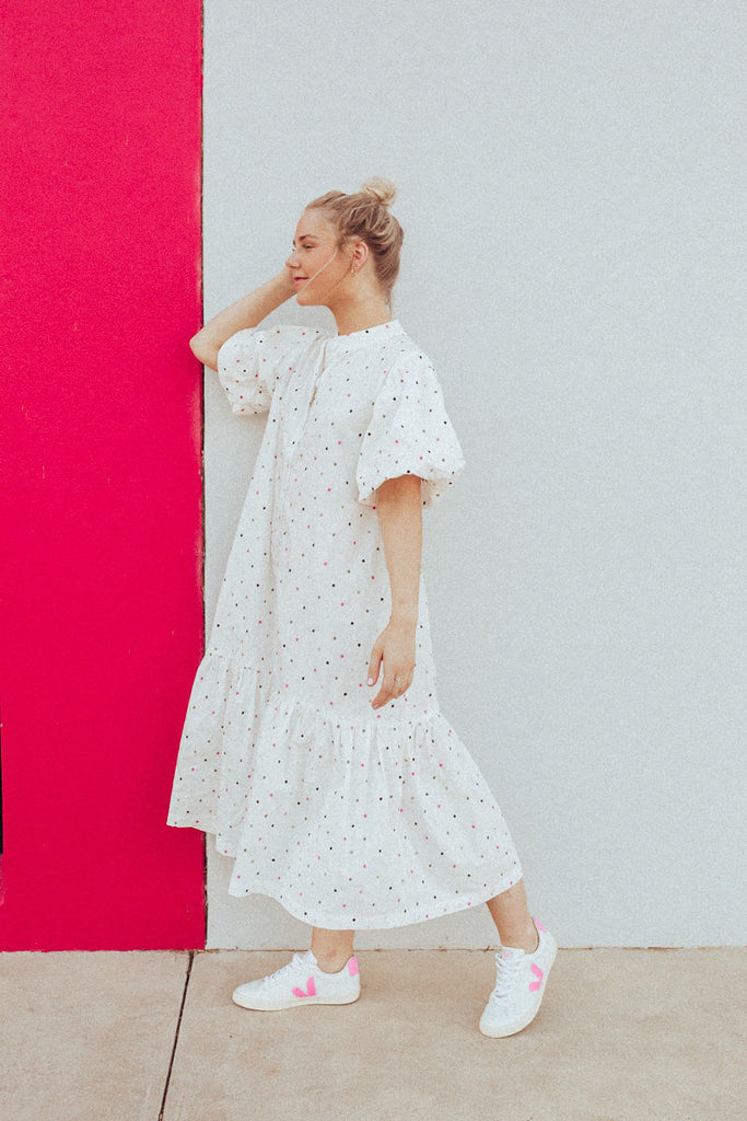 Full length side view of Abby wearing Nice Martin Puff Sleeve dress with spot embroidery detail