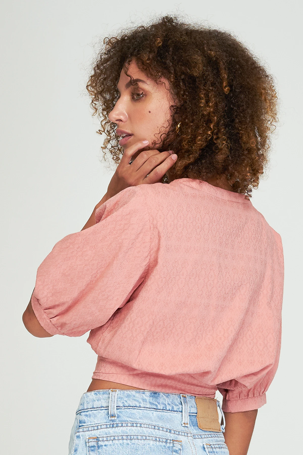 Back up close shot of model wearing Aurora Wrap Top in rosebud pink by Rue stiic