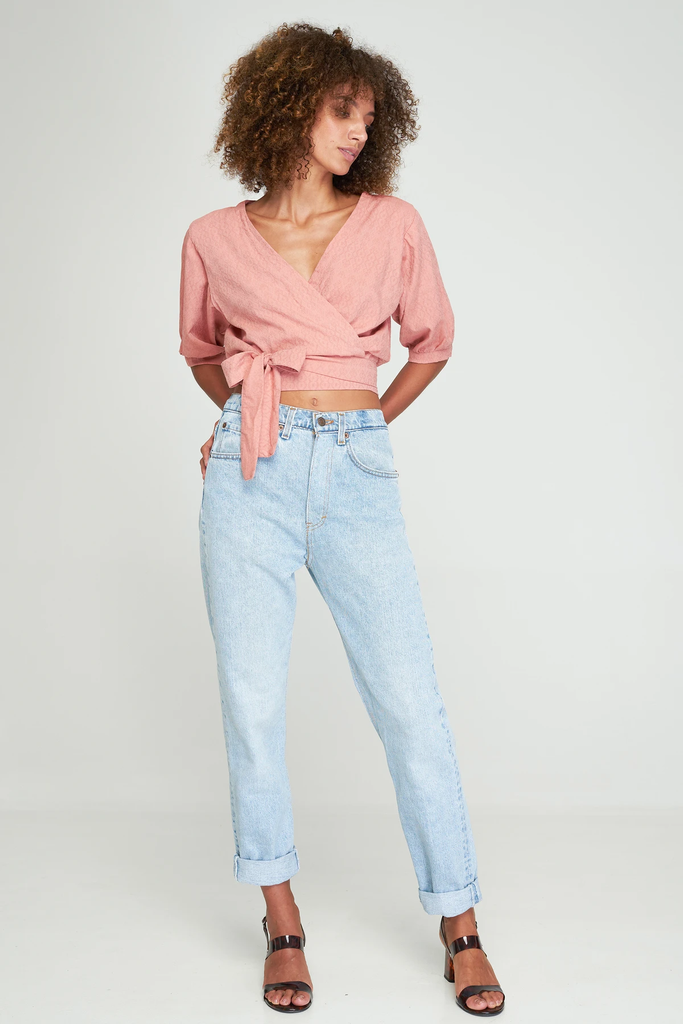 Full length front view of model wearing Aurora Wrap Top in Rosebud pink by Rue Stiic with vintage jeans