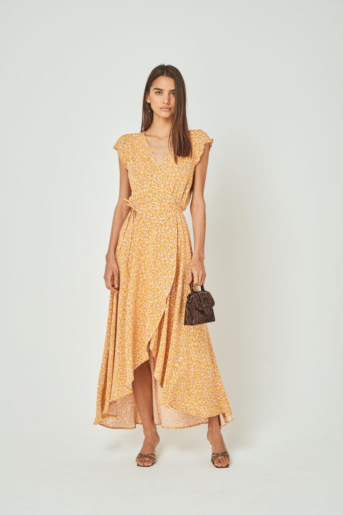 Front view of woman wearing the Auguste Dean Sierra Wrap Maxi Dress in Yellow