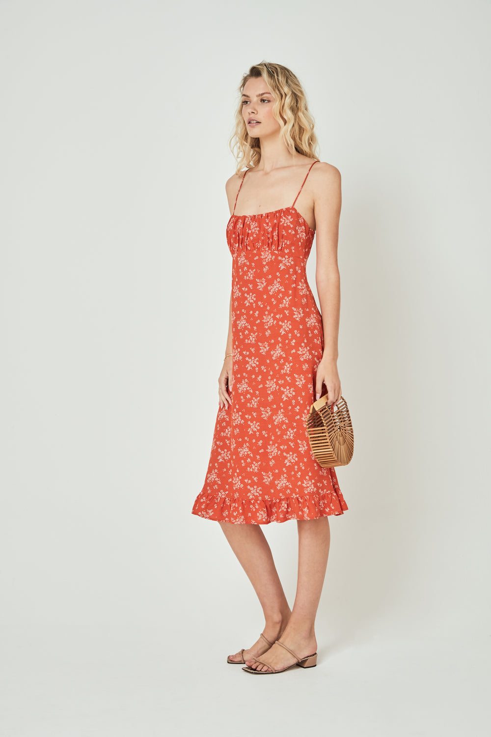 Side view of the Auguste - Meave Davis Midi Dress in Orange with white floral