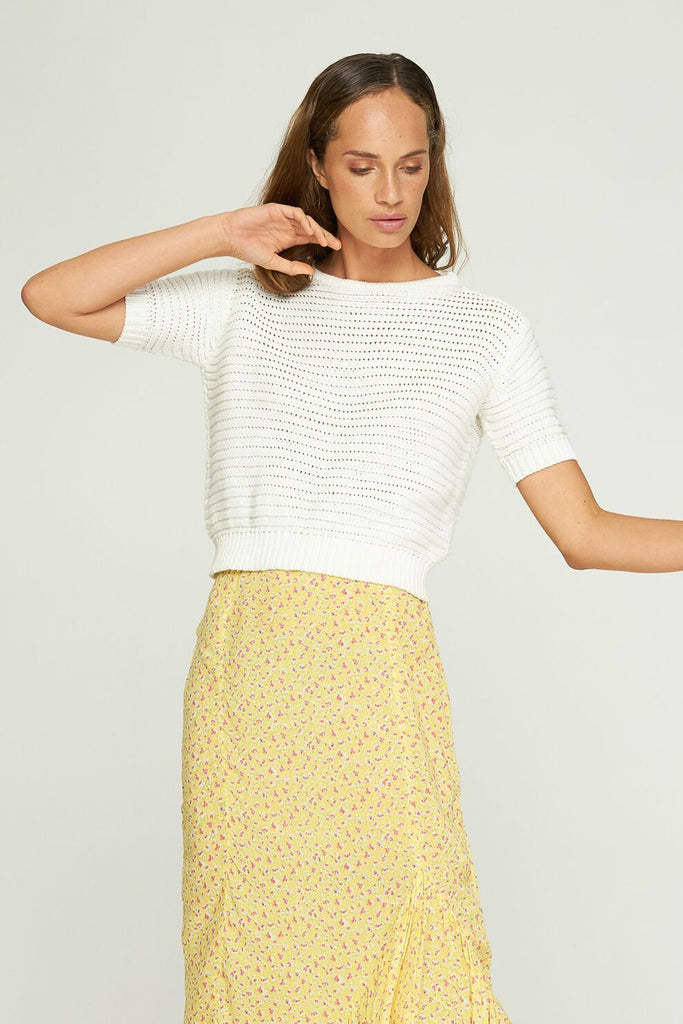 Full length of model wearing Rue Stiic Pele Knit Tee in White with yellow skirt