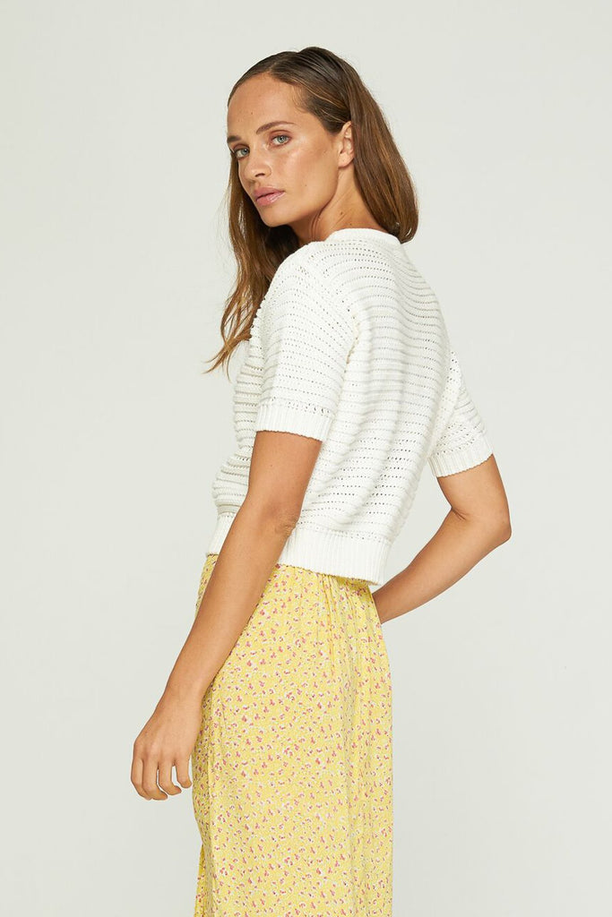 Back view of model wearing Rue Stic Pele Knit in white with yellow skirt