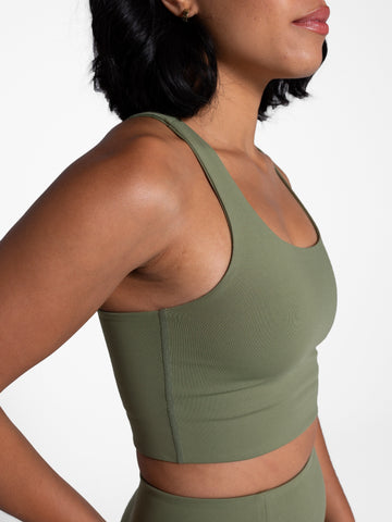 a woman wearing an olive color sports bra