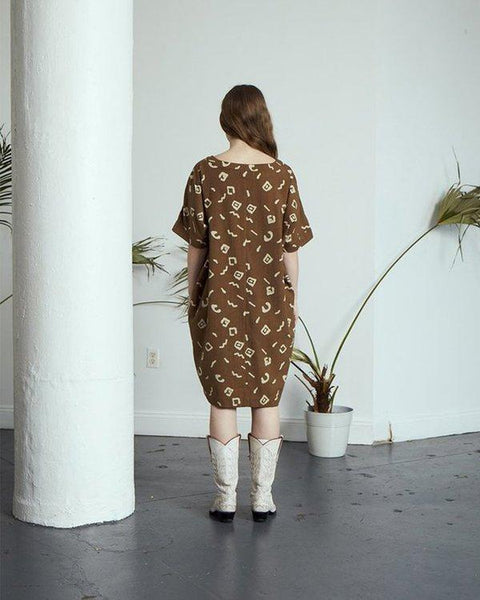 a woman wearing a moss printed tunic and white cowboy boots back view