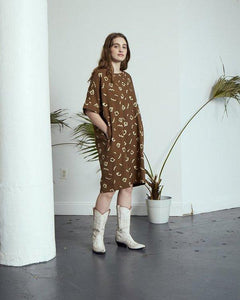 a woman wearing a moss printed tunic and white cowboy boots hands in pockets