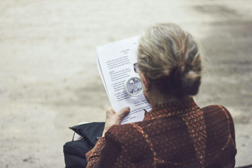 elderly woman reading page with magnifying glass