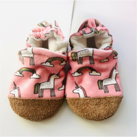 Pink organic cotton fabric with unicorns and rainbows. Infant slipper with soft leather sole