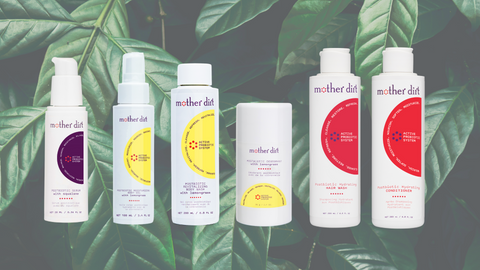 mother dirt serum, body oil, body wash, deodorant, shampoo and conditioner on green plant background