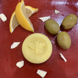 lemon lotion bar with olives, shea butter, and lemon wedges