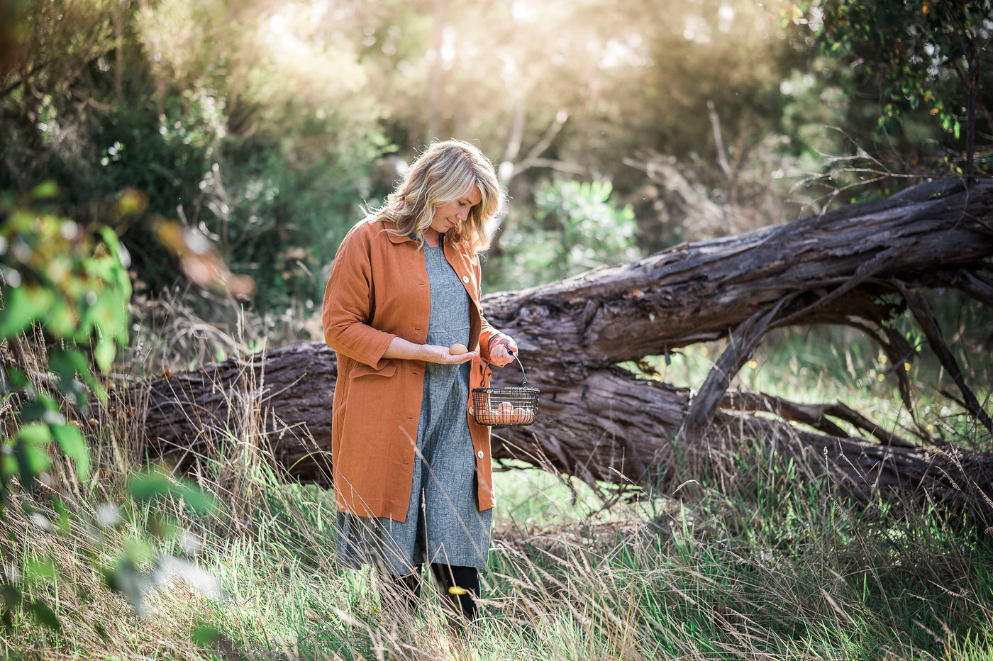 Amy from Ruby Hill organics is standing in a paddock.  She is holding an egg basket in one hand and an egg in the other.  Amy is wearing a line black marle dress from MATTA Clothing.  Over the dress she is wearing an Ochre coloured linen Jacket.