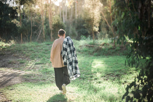 A woman walking along a paddock in the sunshine. She is wearing a pair of black pants, a long sleeve shirt and has a large navy and white check jacket draped across her right shoulder.  All clothes are from MATTA Clothing Australia