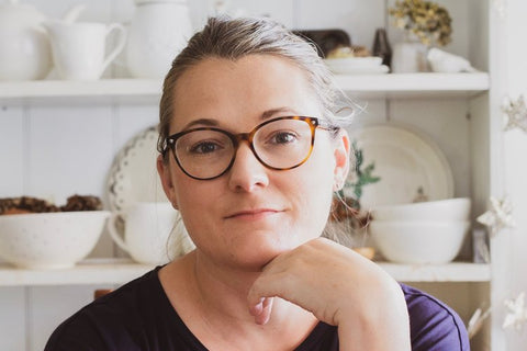 Photo of Christina Lowry sitting in front of a cabinet in her kitchen