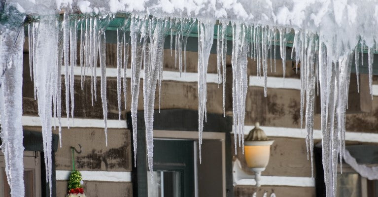 icicles hanging of roof of log cabin