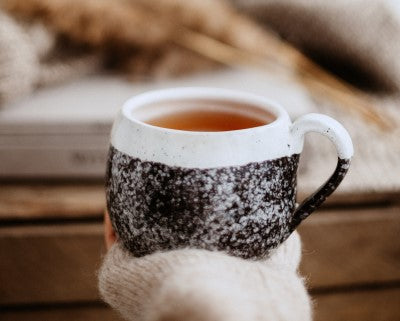 hand holding warm cup of tea