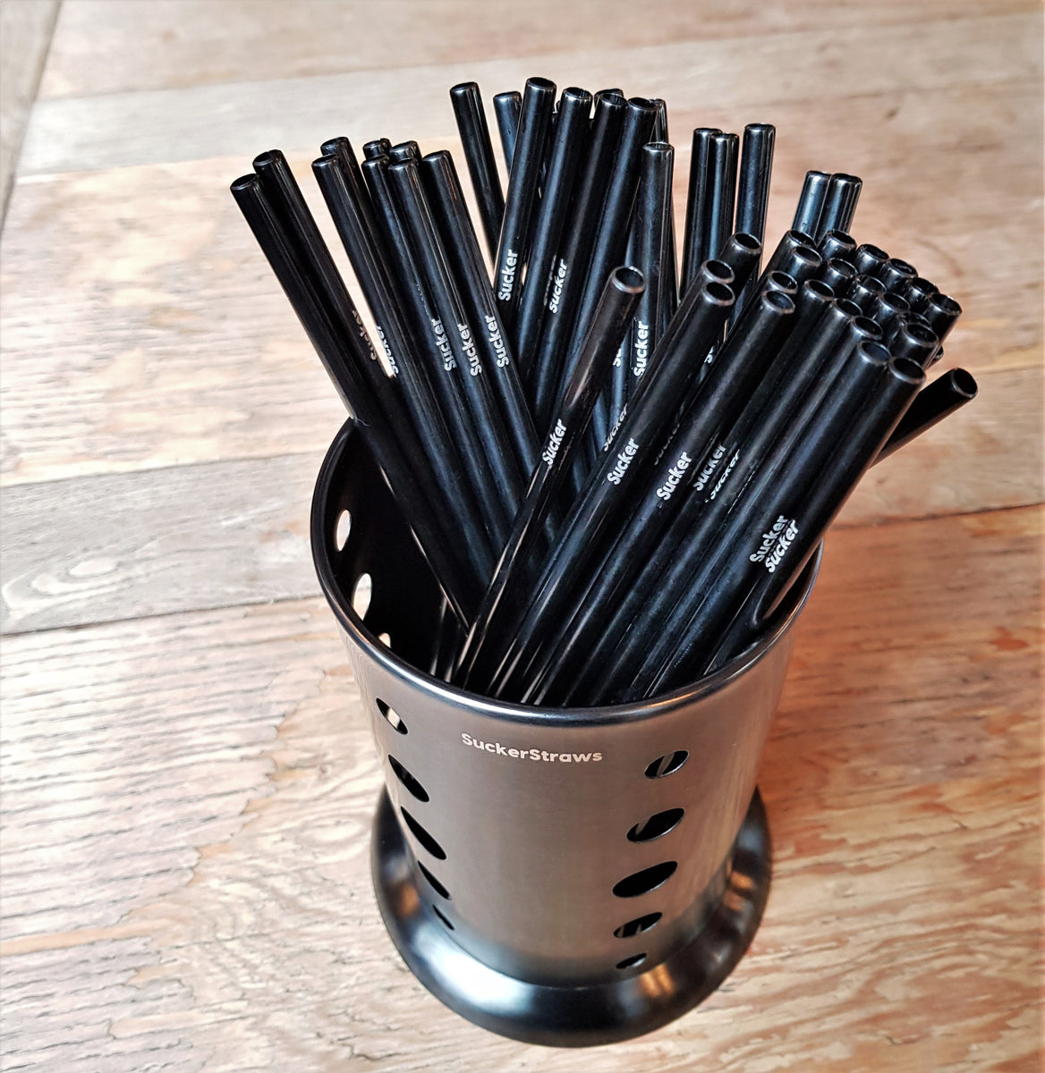 SuckerStraws, bulk sustainable and reusable metal straws shown in the washing basket on a table in a pub bar