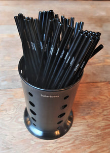 The SuckerStraws glasswasher washing basket with reusable metal straws displayed on a wooden table. SuckerStraws are bulk wholesale reusable metal straws for bars and restaurants available worldwide.