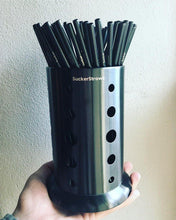 Load image into Gallery viewer, A hand holding up a SuckerStraws glasswasher washing basket with reusable metal straws displayed.  SuckerStraws are bulk wholesale reusable metal straws for bars and restaurants available worldwide.