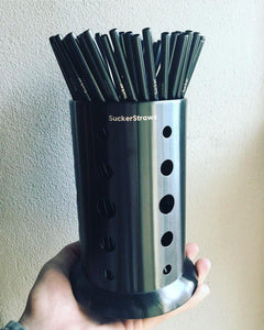 A hand holding up a SuckerStraws glasswasher washing basket with reusable metal straws displayed.  SuckerStraws are bulk wholesale reusable metal straws for bars and restaurants available worldwide.