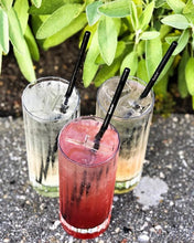 Load image into Gallery viewer, Buy 100 reusable metal SuckerStraws with 10 cleaning brushes - three fruity cocktails shown with black metal straws on a ledge with leafy bushes behind.