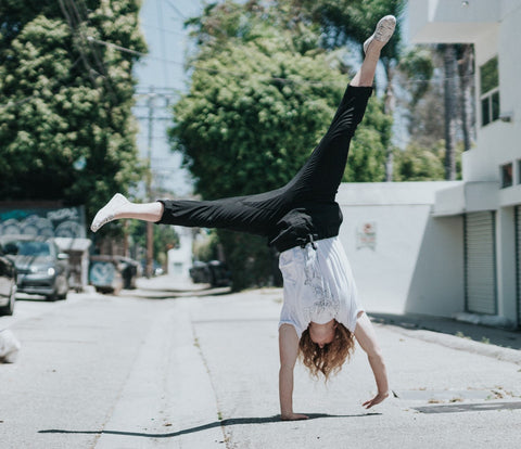 Lady doing a cartwheel in black trousers and a white top