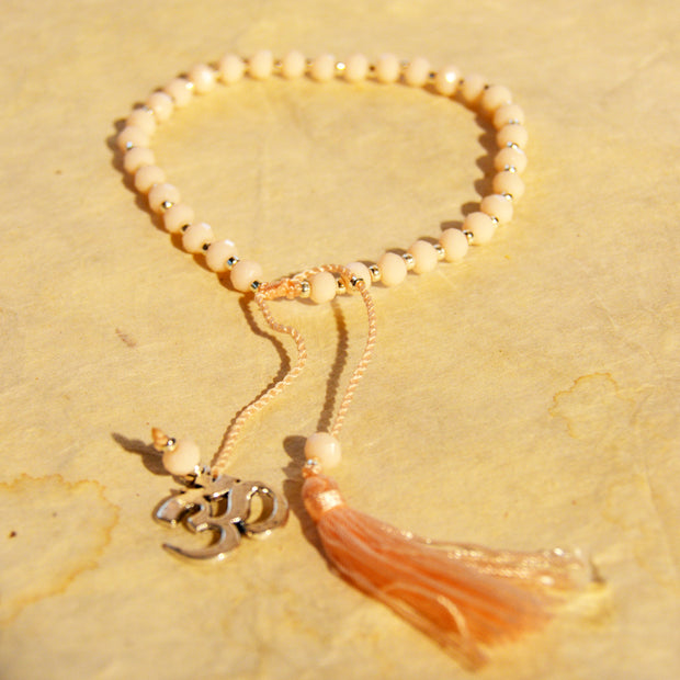 Cream Colored Beaded Bracelet with Om Charm and Tassle