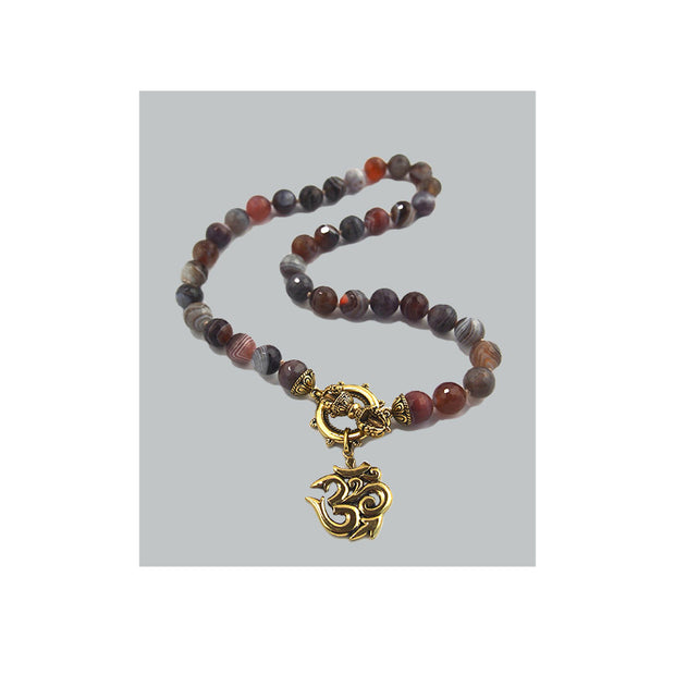 Botswana bead necklace with brass om pendant and dorje toggle front closure