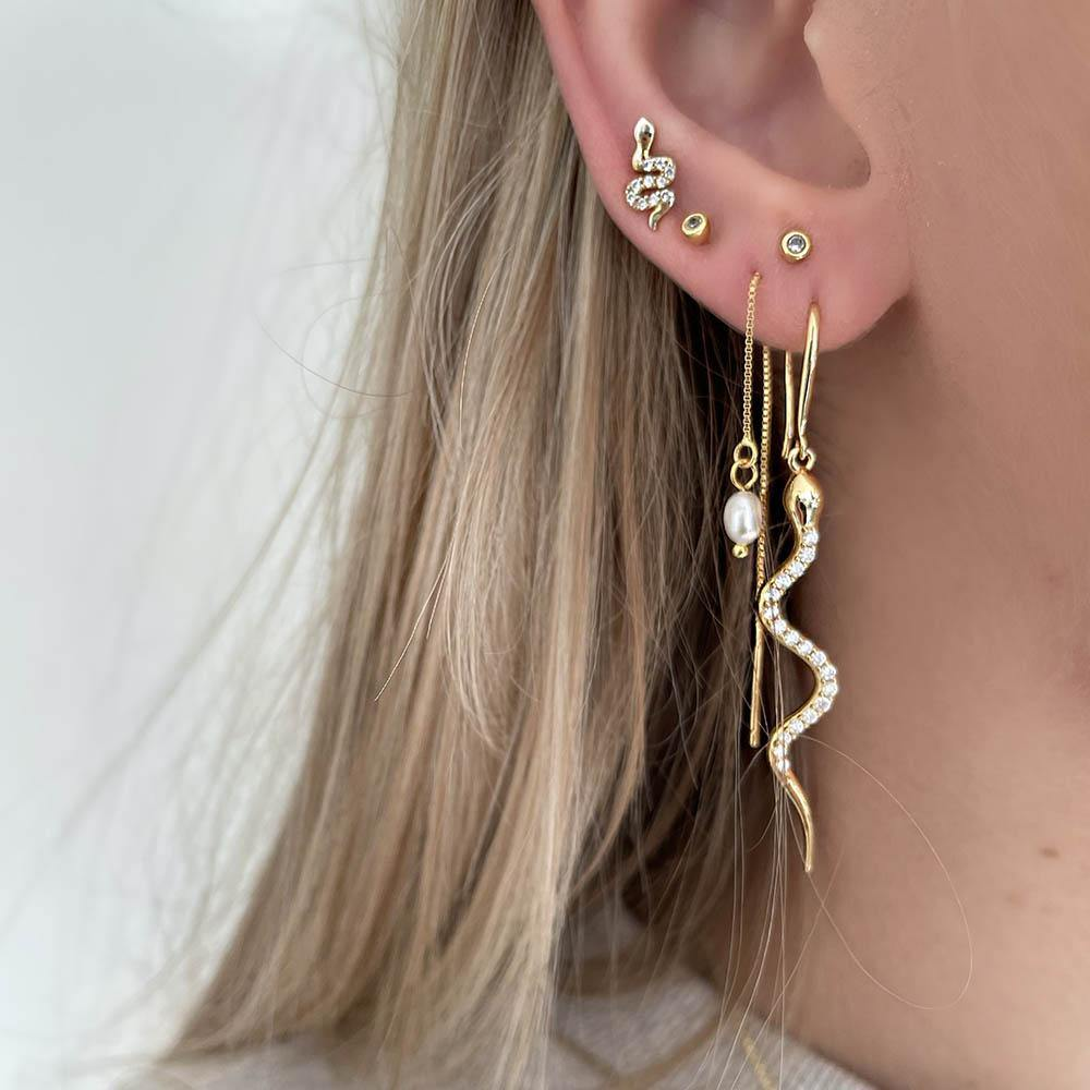Because of their enchanting designs our Boa Earrings are some of our absolut bestsellers. Boa Earrings are long snake earrings filled with clear cubic zirconia, which creates the perfect mix of raw and feminine. Style them alone or together with some of our other earrings to create a stacked look.