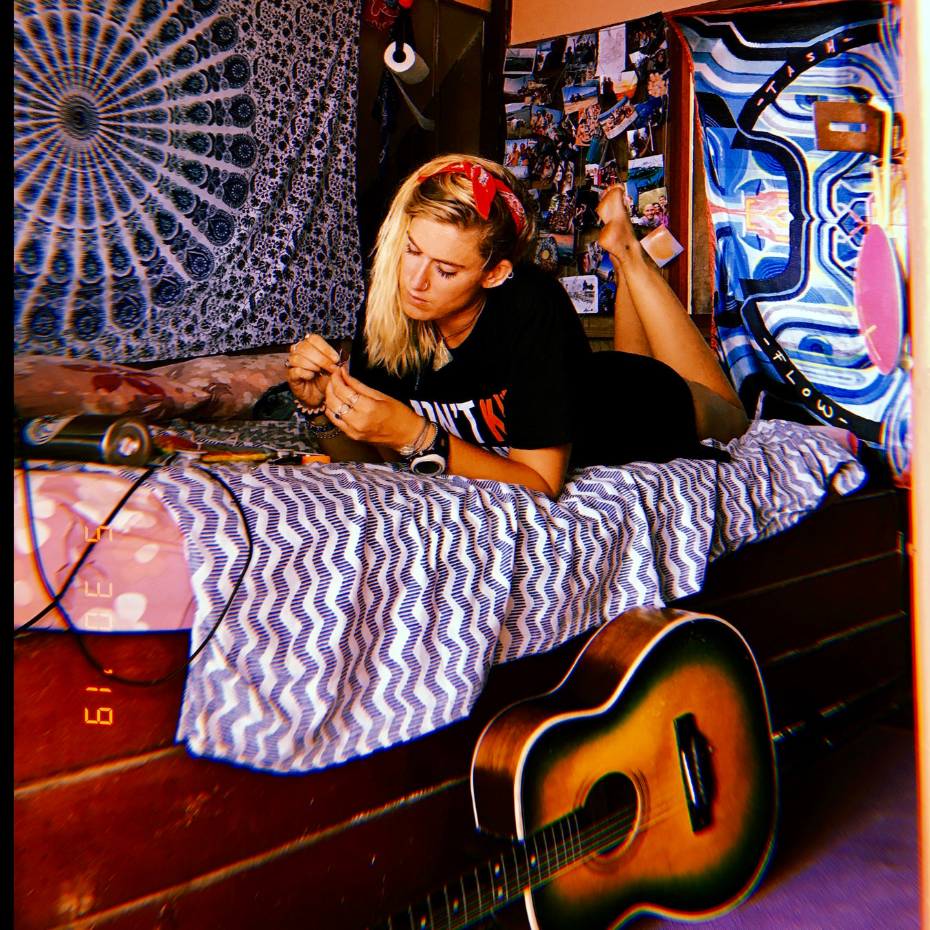 Alice Birnbaum of ABSeas laying on her bed with her guitar at the base