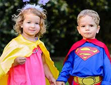 Young boy and girl wearing superhero capes