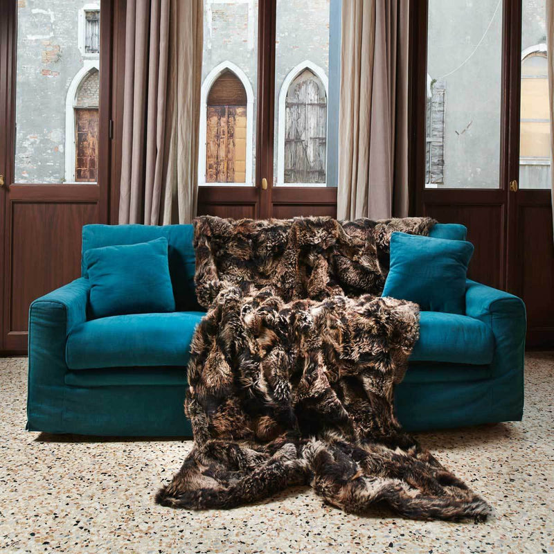 Luxurious full size truffle brown sheep skin fur blanket spread out on a teal blue sofa with glass windows in the background