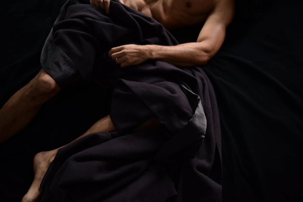 Man lying in bed with black as night henry luxury throw for bed