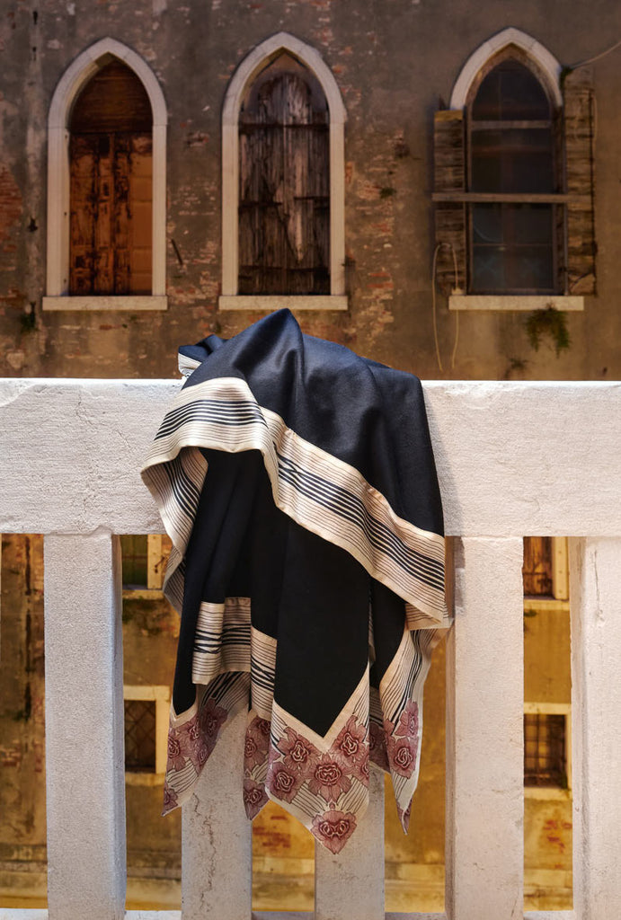 now voyager luxury cashmere blanket with beautiful patterned pure silk borders hanging off a balcony