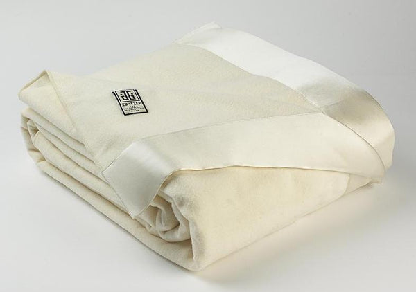 Photo of Henry luxury blanket and throw in white with shining silk borders lying neatly folded.