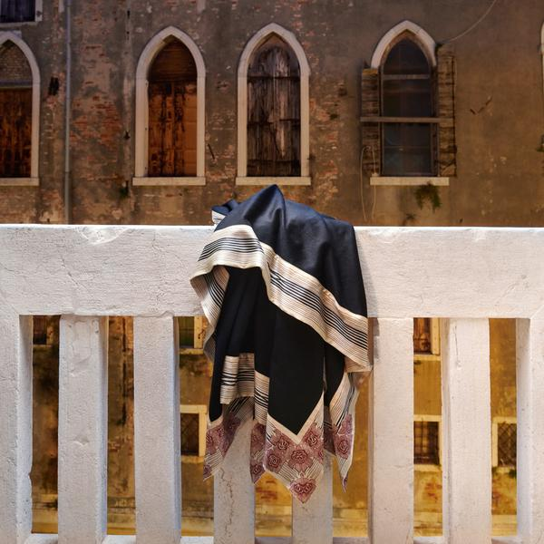 Now Voyager luxury travel throw blanket in black hanging on a scenic balcony during a travel to Venice