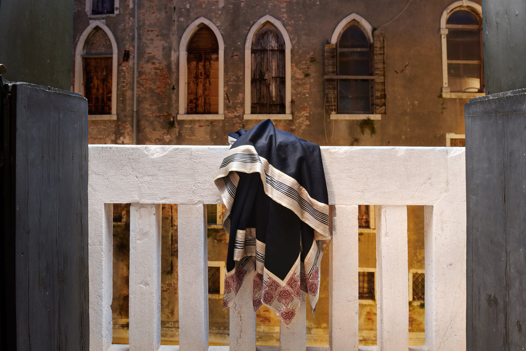 Now Voyager luxury throws and blankets hanging on a balcony in venice with windows in the background